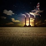 Savior. Surrealism. Naked man with wings in US national colors flies above field of wheat. Factory at the horizon. Human elements were created with 3D software Royalty Free Stock Images