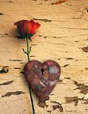 Rusted love. Surrealism. Red rose and rusted heart with keyhole royalty free stock photo
