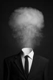 Surrealismus- und Geschäftsthema: der Rauch anstelle eines Hauptmannes in einem schwarzen Anzug auf einem dunklen Hintergrund im  Stockfotografie