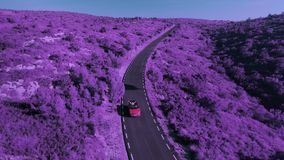 Traveling in convertible car for life. Surrealistic and creative ultra violet or purple aerial drone footage of pantone color of year of two young women best stock footage