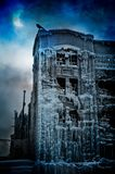 Frozen urban castle: Surrealistic fantasy concept. Surrealistic fantasy concept with a vintage building covered in ice, a solar eclipse shaped like the moon, a royalty free stock image
