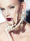 Surrealistic fashion portrait of a woman wearing jewellery. Surrealistic fashion portrait of young beautiful woman with dramatic makeup, wearing jewellery and Stock Image