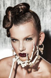 Surrealistic fashion portrait of woman. Surrealistic fashion portrait of young beautiful woman with dramatic makeup, wearing jewellery and holding a skeleton Stock Image