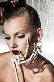 Surrealistic fashion portrait of woman. Surrealistic fashion portrait of young beautiful woman with dramatic makeup, wearing jewellery and holding a skeleton Stock Photography