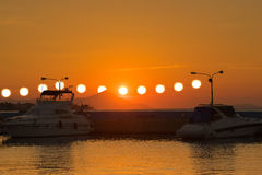 Surrealistic  view of a sunset with multiple suns hanging from the power electricity cables against the boats. Surrealistic  view of the sunset with multiple Royalty Free Stock Photography