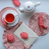 Surrealistic wonderland tea drinking - a mug with flavored pink tea, crocheted napkins, a teapot, toys - fish and dinosaur