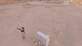 Surrealistisch perceel Een meisje en een witte piano op de achtergrond van een zandkuil en een vrachtwagen Luchtmening stock videobeelden