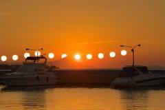 Surrealistische Ansicht eines Sonnenuntergangs mit den mehrfachen Sonnen, die vom Energiestrom hängen, verkabelt gegen die Boote Lizenzfreie Stockfotografie