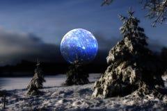 Surrela måne över kallt vinterlandskap Arkivfoton