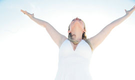 Surrender. A beautiful blond woman happily smiling with arms spread wide against the sky Royalty Free Stock Image