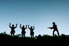 Surrender. Toy soldiers surrender to an armed enemy Royalty Free Stock Photography