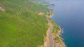 Surret flyger ovanför huvudvägspring mellan kullar och havet lager videofilmer