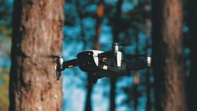 Surret med en kamera svävar i luften Quadcopter flyger ovanför jordningen i skogen stock video