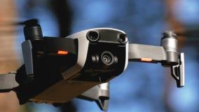 Surret med en kamera svävar i luften Quadcopter flyger ovanför jordningen i skogen arkivfilmer