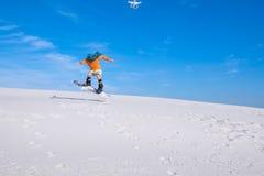 Surret skjuter en man som gör trick på en snowboard Royaltyfri Foto