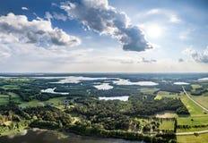 Surrfoto - härlig landskappanorama på sunnny sjöar för sommardag, skogar och blå himmel arkivbilder