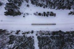 Surrfotografi av den vinterskogen, lokomotivet och järnvägen arkivbild