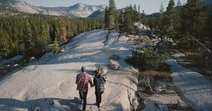 Surrkameran följer unga romantiska par som tillsammans fotvandrar längs att förbluffa vit, vaggar på den Yosemite nationalparksko arkivfilmer