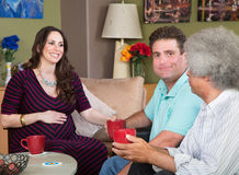 Surrogate Mom with Male Couple. Happy male friends having coffee with surrogate mother Royalty Free Stock Image