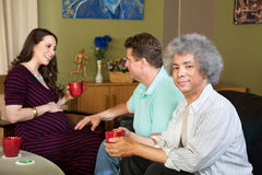 Surrogate mother with two same sex parents. Black men with male partner and pregnant surrogate female Royalty Free Stock Photo