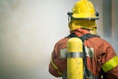 Surround пожаротушения пожарного с темным дымом Стоковые Фото