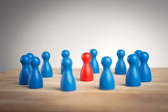 Surrounded by adversity or praised for being different concept. With figurines Stock Photos