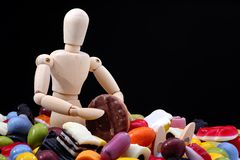 Surrounded by candy. Wooden mannequin, surrounded by candy, holding a cookie royalty free stock images