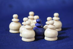 Surrounded chess pawn. Details of group of white chess pawns surrounding single blue one Royalty Free Stock Image