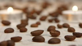 Surrounded by coffee beans candles burning on a white table. Focus frame starts with toasted coffee beans and the background swaying candlelight, two white stock footage