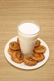 Surrounded by cookies. Glass of milk surrounded by chocolate chip cookies Stock Photos