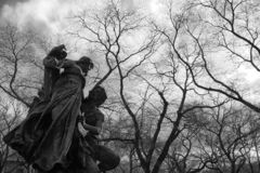 Surrounded by a crown of bare branches of trees, a sculpture representing a devoted man and a woman, both mythological figures. Black and white view of a royalty free stock images