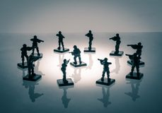 Surrounded soldier. Toy soldier surrounded by enemy infantry Stock Image