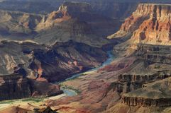 Surrounding the Colorado River, the Grand Canyon takes on an orange hue under the setting sun. royalty free stock image