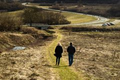 Older couple walk in nature. Fields by the road with dry plants. Beautiful sunny winter day. stock photo