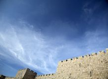 Old Jerusalem City Wall. The surrounding wall of the old city of Jerusalem beneath a spectacular cloudy blue sky Stock Images