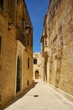 The narrow street of Mdina, the old capital of Malta. In the surroundings of limestone walls. The narrow medieval stone paved street of Mdina, the old capital Royalty Free Stock Images