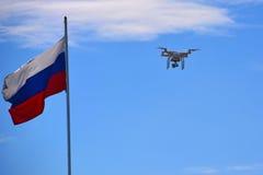 Surrquadcopter med den digitala kameran i flykten Surr med den digitala kameran som flyger över en Ryssland flagga Arkivfoto