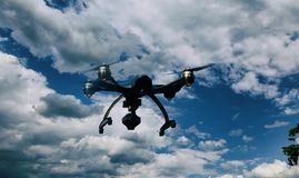 Surrquadrocopter med kameran som flyger över skog arkivbild
