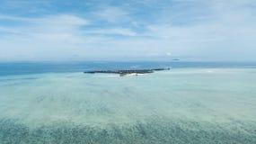 Surrsikt av en semesterort över en rev som omges av klart vatten royaltyfri bild