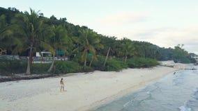 Surrsiktskvinna som går på den sandiga stranden på havskust Flyg- landskapflicka som går på den tropiska stranden på horisont lager videofilmer