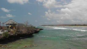 surrvideo för flyg 4K av den unga kvinnan som tar foto på den tropiska lösa steniga stranden Bali ö stock video
