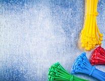 Surtido de bridas de plástico plásticas multicoloras en el metal rasguñado Foto de archivo