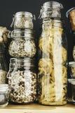 Surtido de granos, de cereales y de pastas crudos en los tarros de cristal en la tabla de madera El cocinar sano, limpia la consu fotografía de archivo