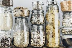 Surtido de granos, de cereales y de pastas crudos en los tarros de cristal en la tabla de madera El cocinar sano, limpia la consu imagen de archivo