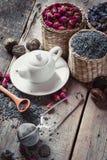 Surtido de la tetera y de la infusión de hierbas: lavanda, rosas, té verde Imagenes de archivo