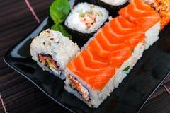 Surtido de los rollos de sushi en la placa negra Fotografía de archivo