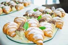 Surtido de pasteles frescos en la tabla en comida fría Cruasanes y tortas Imagen de archivo
