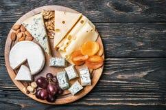 Surtido de queso con las frutas y las uvas en una tabla de madera Fotografía de archivo