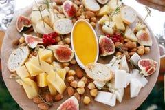 Surtido de queso en el tablero de madera Bocados en la tabla de comida fría imagen de archivo