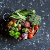 Surtido de verduras frescas - bróculi, calabacín, tomates, pimientas, habas verdes, remolachas, ajo en una cesta del metal Imagen de archivo